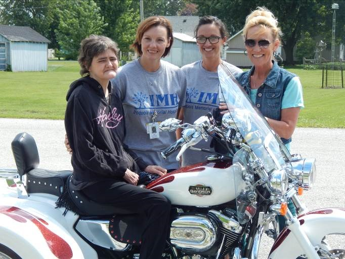 07-06-2017 Hospice fulls wish of patient - Sharon Linback, on the motorcycle, with Hospice staff members (lt-rt) Traci Bishop LCSW, Tammy Barragree, and Teri Reffett, RN,