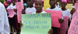 Girls in Uganda carrying an MH Day sign