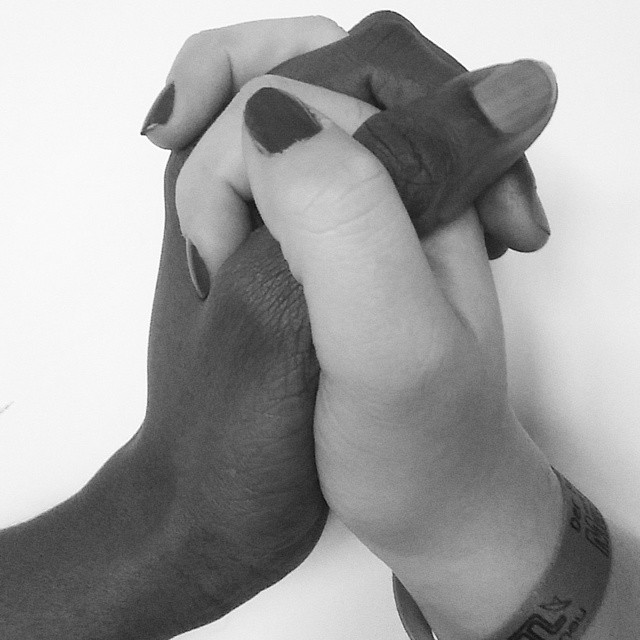a black hand and a white hand clasping racism sexism | imjussayin.com