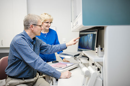 Dr. Immel and assistant examining a dental x-ray