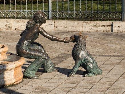 Statue einer Frau mit spielendem Hund