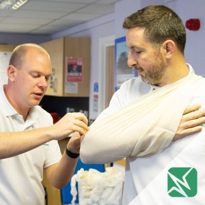 application of triangular bandage as sling with green Immerse Training logo
