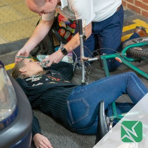 casualty with bike by car receiving oxygen with green Immerse Training logo