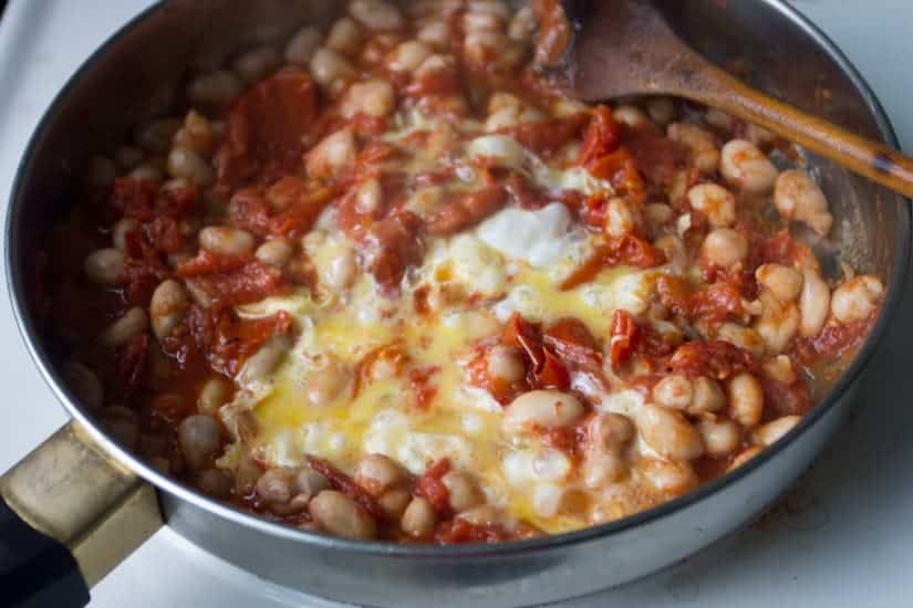 You simply can't stop eating these borlotti beans in tomato sauce with eggs. They're saucy, spicy and so meaty!