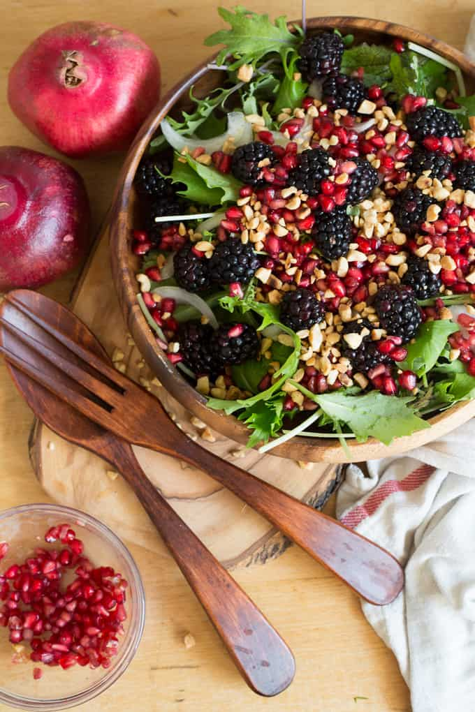 Berry salad with red onions, arugula, nuts and pomegranate arils