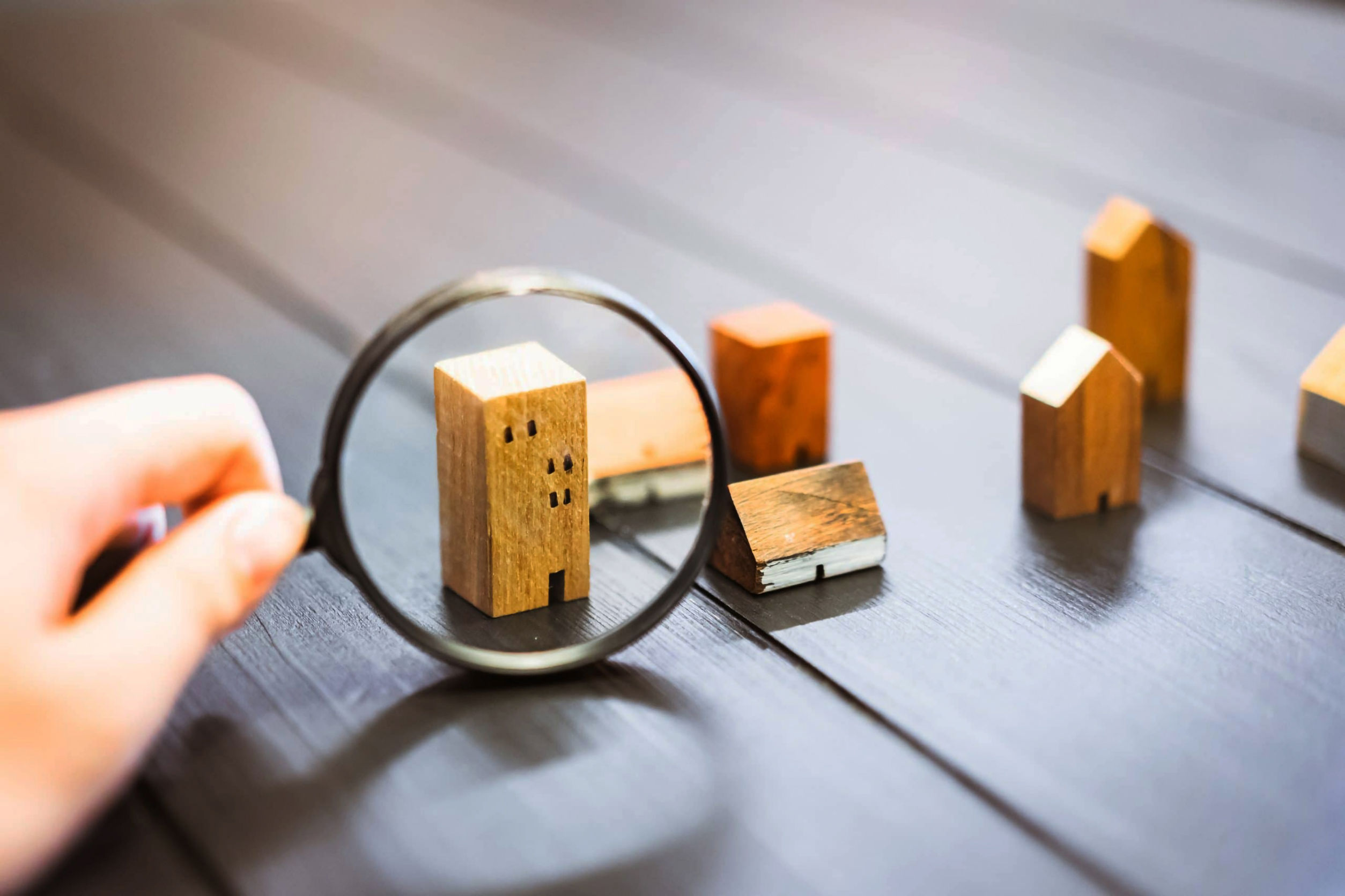 Hand holding magnifying glass and looking at house model.