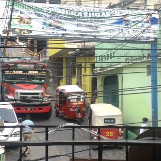 Chicken buses and tuk tuks battle the main corner