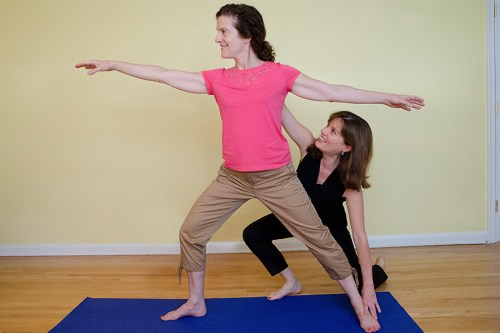 Imogen helps this student improve her coordination doing a yoga pose