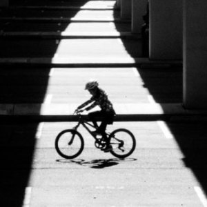 Cyclist in shadow of freeway
