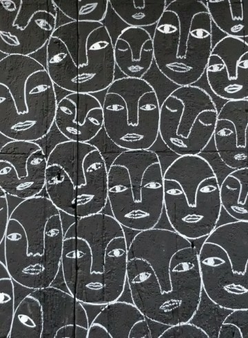 simple chalk drawings of many faces on a black wall