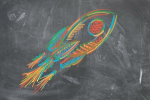 a rocket drawn on a blackboard with yellow, red, green and blue chalk