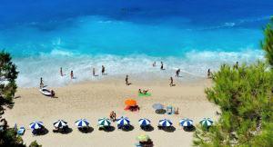 Beach in Greece with blue sea and sun umbrellas