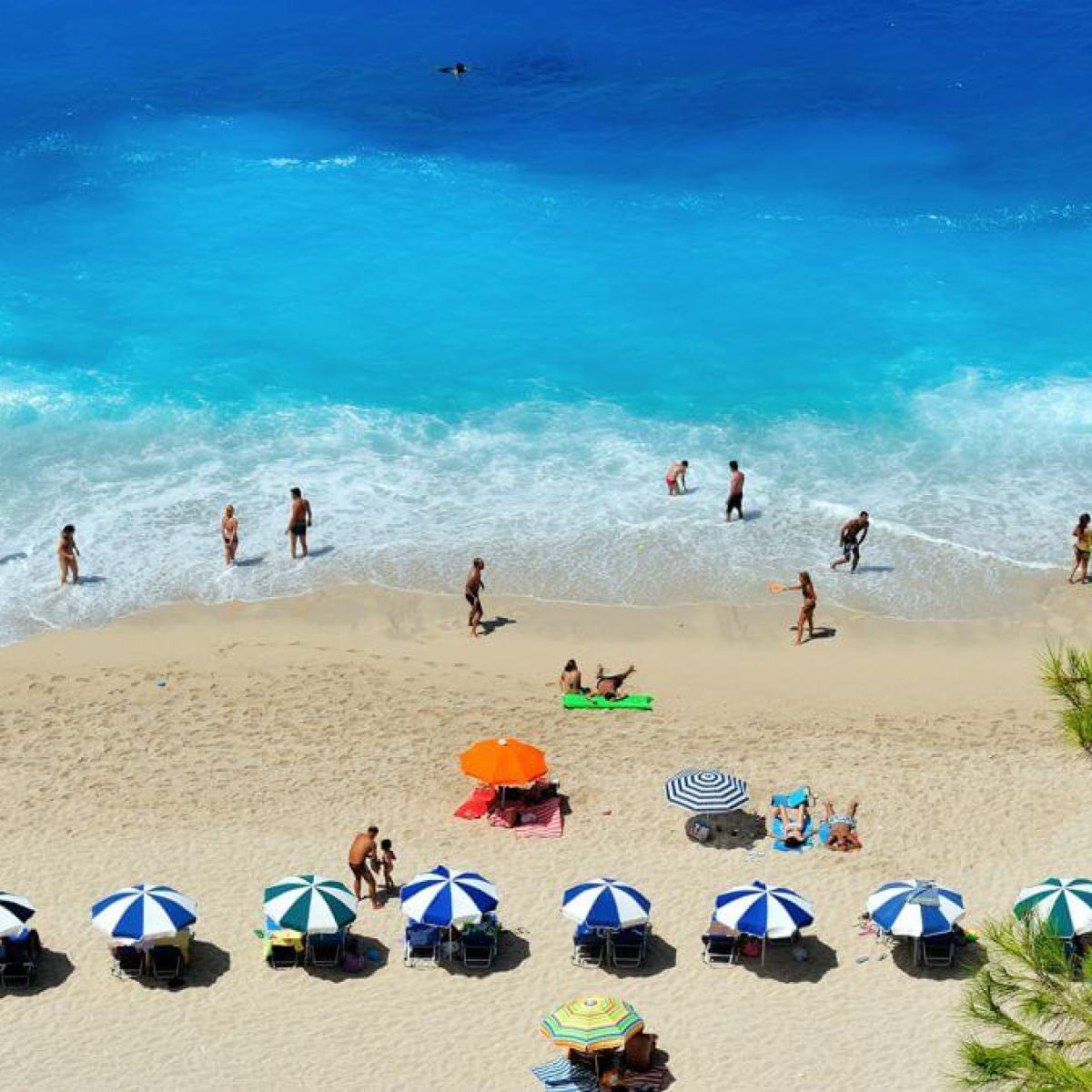 Beach in Greece with blue sea and sun umbrellas