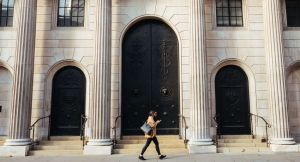 Woman walking past the front door of the Bank of England