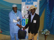 Oseni Pelumi, the best student in Mathematics (SSS I) receiving his prize from Alhaji Bolarinwa