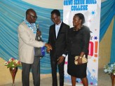 Oluwafemi Ifemide, the student with best SSCE result (M) being presented with his prize by Sola Awoye. Standing left was his mother