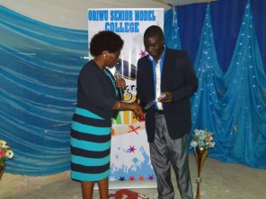 Mr Oketade Awotunde receiving his Outstanding Teacher of the Year 2015 from a Director, Ministry of Education.