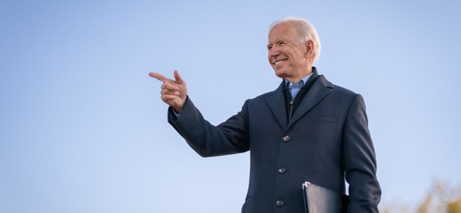 Photograph of Joe Biden holding a black portfolio, smiling and pointing at an unseen crowd.