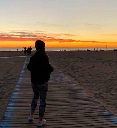 An image of a person standing on a beach in the sunset