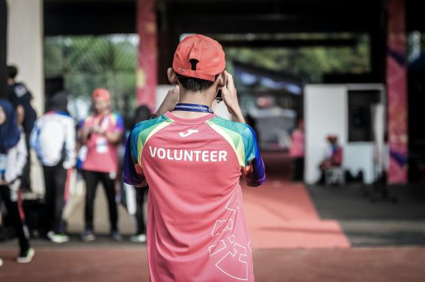 An image of a man with his back to the camera and a shirt saying volunteer