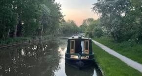 Photo of a single canal boat on the side of the canal with a sunset in the backdrop and trees lining the sides of the canal