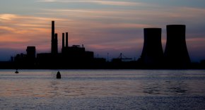 Photo of the silhouette of a power plant in the sea in front of a sunset.