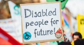 Photo of a sign saying 'disabled people for future', held up amongst protesters