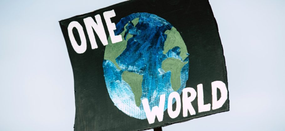 Photo of a sign being held up against a white background with the words 'one world' and planet earth on it