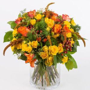 Bouquet dai toni caldi con rose arancio, rose a grappolo, garofani verdi e fiorellini di stagione