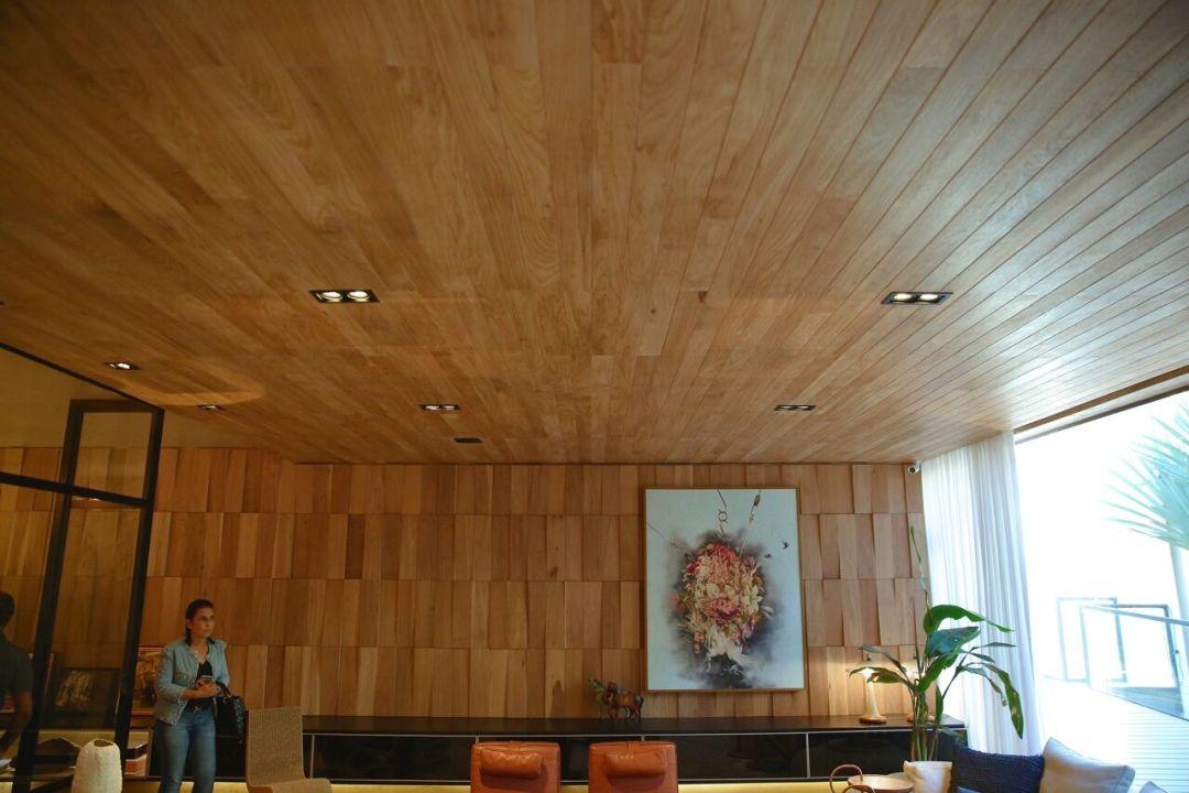 Painéis esculturais em madeira de demolição apaixonante e forro, tudo em madeira clara.