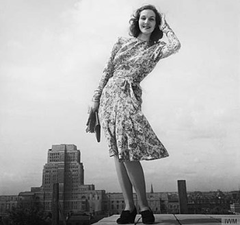 A model wears a wartime dress on a Bloomsbury rooftop.Senate House, the headquarters of the Ministry of Information, is clearly visible behind her. © IWM (D 14820)