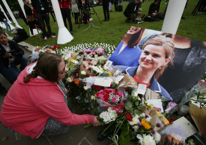 File photo dated 17/06/16 of a woman leaving flowers in Parliament Square, London, after Labour MP Jo Cox was shot and stabbed to death in the street outside her constituency advice surgery in Birstall, West Yorkshire, one of the most significant events in the EU referendum campaign.