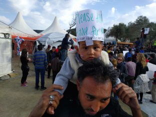 An Afghan child joins a protest at Moria