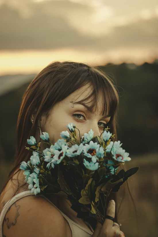 woman holding flowers on focus photography