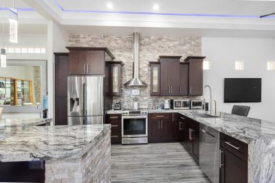 Kitchen with dark cabinets countertop, backsplash and stainless steel appliances