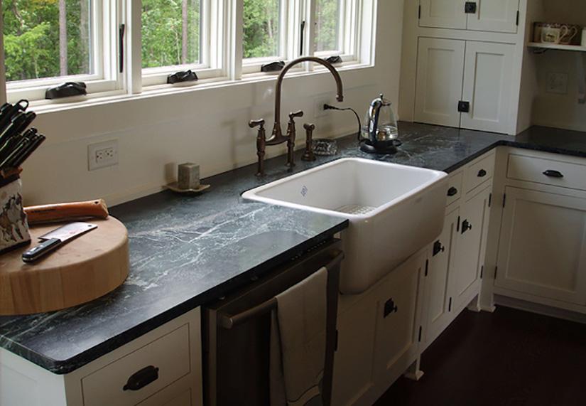Kitchen with farm sink, soapstone countertops, backsplash and appliances