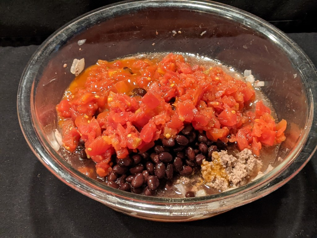 Add tomatoes, black beans and 1/4 of enchilada sauce to ground beef mixture.  Heat for 2 minutes