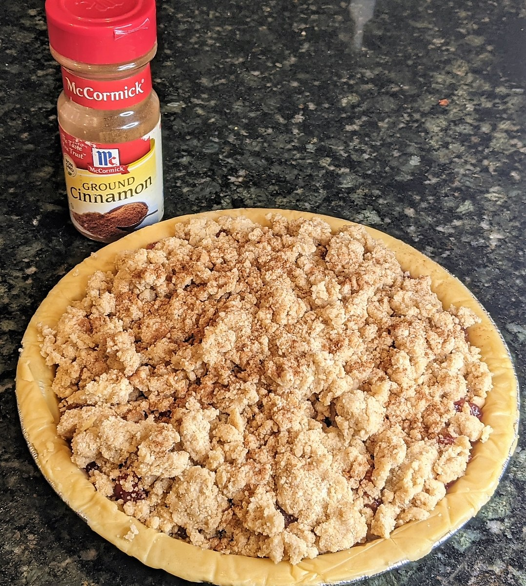 topping on pie with jar of ground of cinnamon