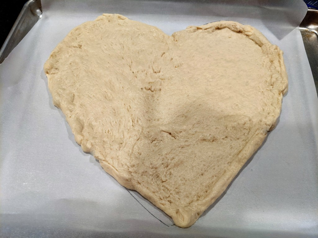 Pizza dough formed in the shape of a heart.