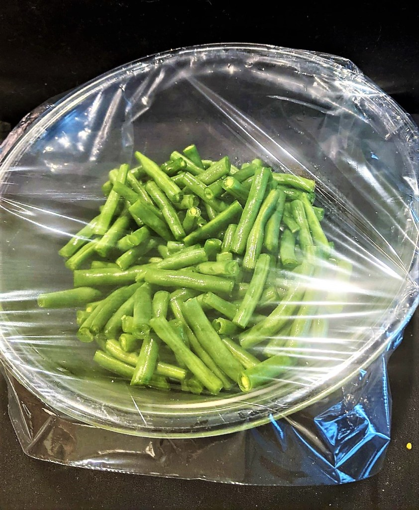 green beans into a microwave-safe dish with 1-2 tablespoons of water and cover with plastic wrap.