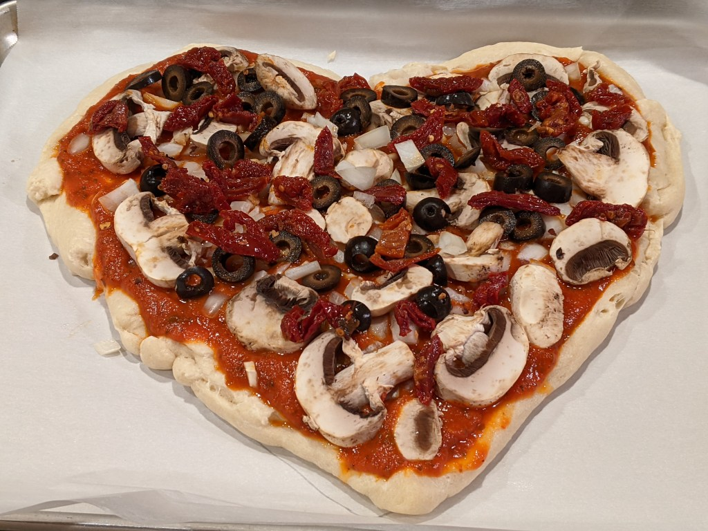 Mushrooms, olives, onions, garlic and black olives on top of pizza sauce