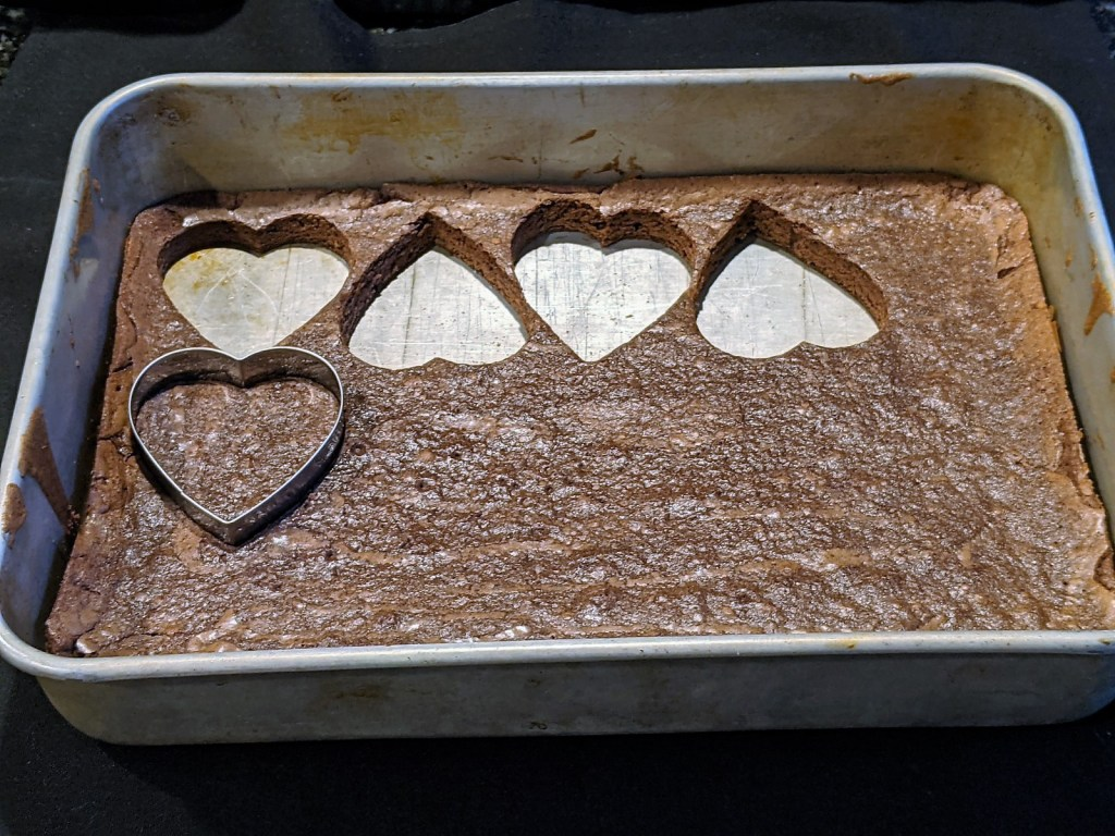 brownies being cut into hearts with a cookie cutter