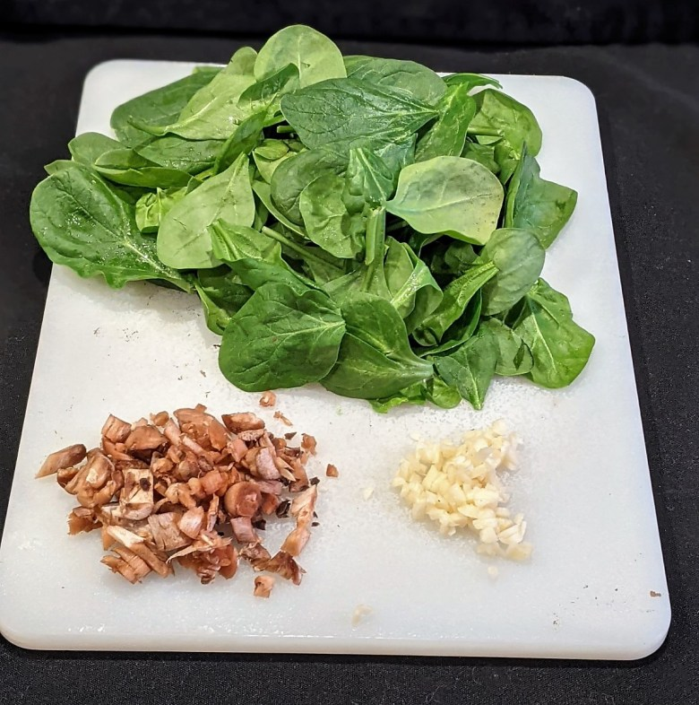 Prep the spinach by removing stems. Mince the garlic and chop the mushroom stems.