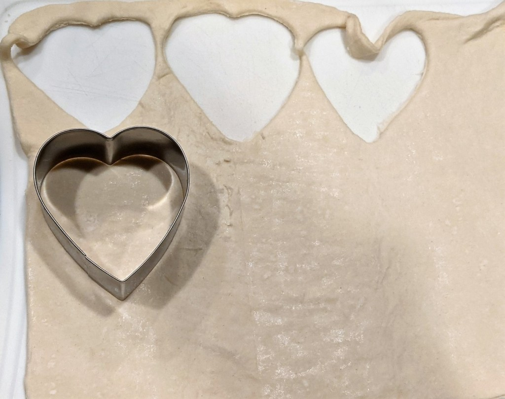 Roll out the puff pastry on a cutting surface lightly sprinkled with flour.  Use heart-shaped cookie cutter to cut.