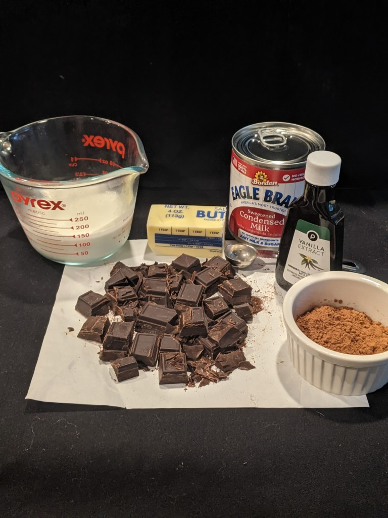 Break unsweetened chocolate into small pieces, measure out heavy cream, butter cocoa powder, open sweetened condensed milk and vanilla