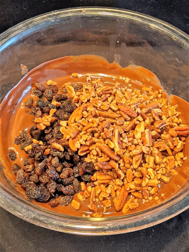Bowl with melted chocolate, raisins and chopped nuts