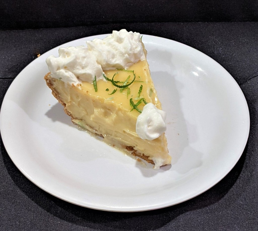 Slice of pie with whipped topping and lime zest