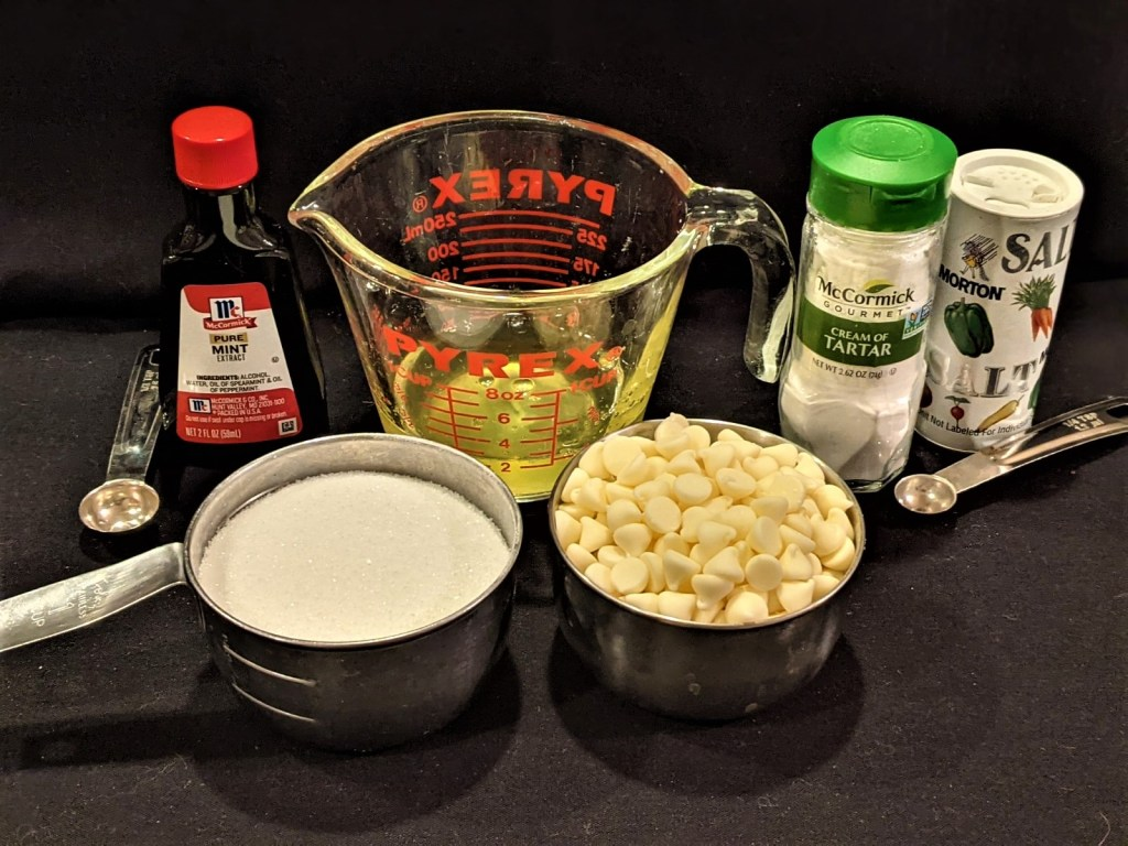 egg whites in measuring cup, sugar and w;hite chips in measuring cups, mint extract, cream of tartar and salt with measuring spoons.