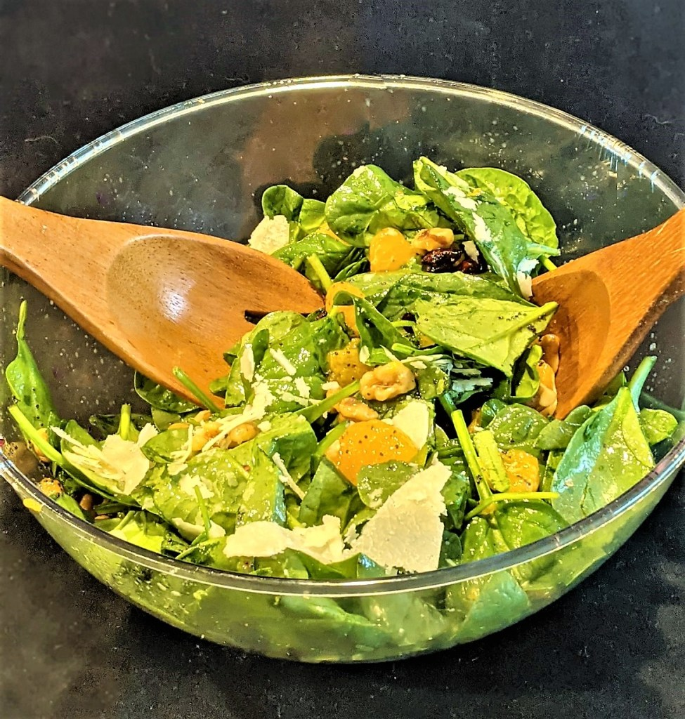 bowl of salad with serving fork and spoon