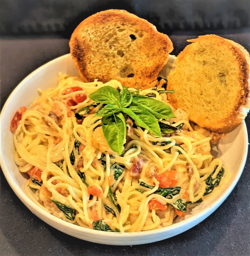 bowl of pasta with two slices of garlic bread